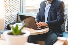 Male using notebook computer in apartment. Man working on laptop while sitting at table in comfortable office Stock Photo