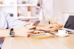 Male using phone and laptop. Male hand using smartphone and laptop at wooden desk in office Royalty Free Stock Photo