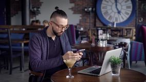 Male using phone while sitting in cafe. Young man using phone while sitting in cafe with drink and laptop. Young man using phone while sitting in cafe with stock footage
