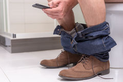 Male using phone while sitting on a toilet bowl. Male wearing jeans and shoes using phone while sitting on a toilet bowl in  the modern tiled bathroom at home Royalty Free Stock Image