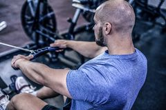 Male using rowing machine at fitness club. Young man doing exercises on fitness machine in gym. back view. dressed in sportswear royalty free stock photos