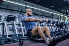 Male using rowing machine at fitness club. Young man doing exercises on fitness machine in gym. Side view royalty free stock images