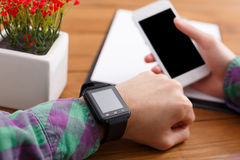 Male using smart watch at workplace, close up, side view, Royalty Free Stock Photo