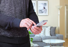 Male using smartphone at home. Male using smarphone with background of the room interiors Stock Image