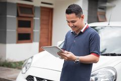 Male using tablet pc. Young asian male using tablet pc in front of his car Stock Photo