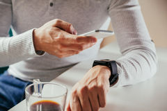 Male Using Technology. Close Up Of Male Synchronizing Smart Watch And Smart Phone Stock Images