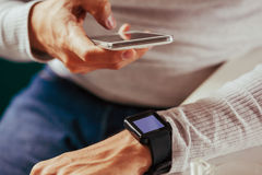 Male Using Technology. Close Up Of Male Synchronizing Smart Watch And Smart Phone Royalty Free Stock Images