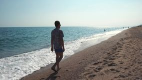 Alone man is strolling on seacoast in summer vacation in daytime. Male vacationer is walking alone over sunny beach in daytime. He is relaxing and enjoying sea stock video