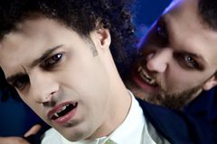 Male vampire attacking other desperate vampire looking camera. Angry male vampires looking camera Stock Photos