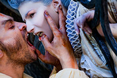 Male vampire biting woman. Close-up of male vampire with wounds biting women in medieval dress Royalty Free Stock Photography