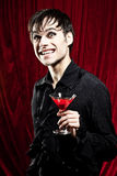 Male vampire with a bloody drink. Male vampire smiling dangerously, his fangs can be seen Stock Photos
