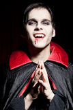 Male vampire with a dangerous smile. Waiting for his next prey Royalty Free Stock Image