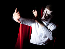 Male vampire defense light. A young male vampire protecting himself from bright light Royalty Free Stock Photos