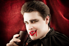 Male vampire Drinking blood smiling. Dangerous male vampire Drinking blood holding a glass Stock Images