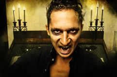 Male vampire with evil eyes. Opening mouth Royalty Free Stock Image