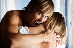 Male vampire is going to bite into a neck. Male vampire is going to bite into the neck of a blond women Royalty Free Stock Image