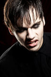 Male vampire with open mouth looking down. Showing his teeth. He's wearing a black shirt. Taken in a studio in Vienna, Austria Royalty Free Stock Photography