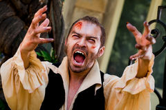 Male vampire roaring. Wounded male vampire raising his arms and screaming Royalty Free Stock Photo