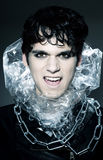 Male vampire showing his fangs. He's wearing a black leather jackets, some chains and a collar out of plastic Stock Photography