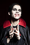 Male vampire smiling dangerously. His fangs can be seen and blood is flowing down at the side of his mouth Royalty Free Stock Photos