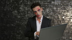 Male vampire uses the laptop. Man in the image of the vampire posing on black background of a brick wall. Halloween concepts and costumes stock footage
