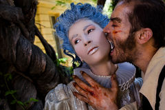 Male vampire zombie biting woman. Male vampire with wounds biting young women in medieval dress Stock Photos