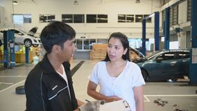 Male vehicle technician having conversation with customer about car repairing budget cost and insurance. Asian woman listening to. Mechanic at maintenance stock video