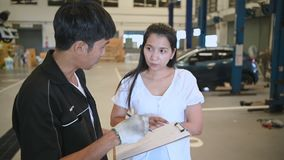 Male vehicle technician having conversation with customer about car repairing budget cost and insurance. Asian woman listening to. Mechanic at maintenance stock video footage