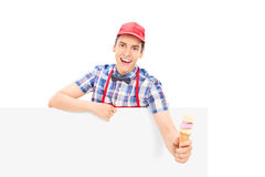 Male vendor holding an ice cream behind a panel Royalty Free Stock Image