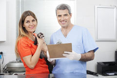 Male Vet Holding Clipboard By Woman With Weasel. Portrait of smiling male vet holding clipboard by women with weasel in clinic Royalty Free Stock Photography