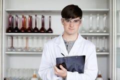 Male vetenskapsdeltagarewriting på en clipboard Arkivbilder
