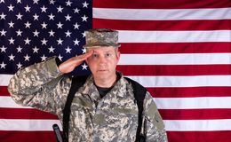 Male veteran solider saluting with USA flag in background while. Veteran male soldier, facing forward, saluting with USA flag in background. Soldier armed with Stock Images
