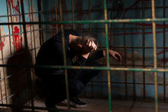 Male victim imprisoned in a metal cage with a blood splattered w Stock Photos