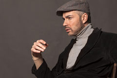 Male vintage style. Handsome pensive man in a jacket and with a cap in vintage style Royalty Free Stock Image