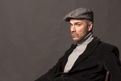 Male vintage style. Handsome sad man in a jacket and with a cap in vintage style Stock Photos