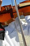 Male violinist creates music. A violinist in a long sleeve white shirt runs the bow across the strings of a violin Royalty Free Stock Photography