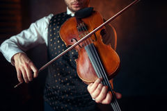 Male violinist playing classical music on violin. Fiddler man with musical instrument Royalty Free Stock Image