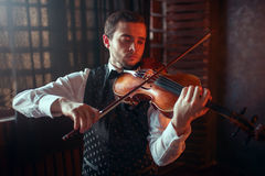 Male violinist playing classical music on violin Royalty Free Stock Images