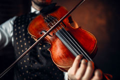 Male violinist playing classical music on violin. Fiddler man with musical instrument Stock Photos
