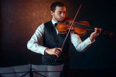Male violinist playing classical music on violin. Fiddler man with musical instrument Stock Photography