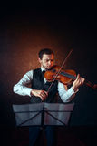 Male violinist playing classical music on violin. Fiddler man with musical instrument Stock Image
