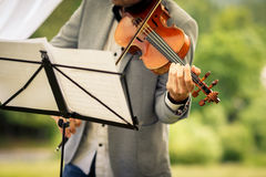 Male violinist playing his instrument and reading a music sheet. During an outdoor summer wedding ceremony (shallow DOF; color toned image Stock Image