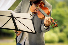 Male violinist playing his instrument. And reading a music sheet during an outdoor summer wedding ceremony shallow DOF; color toned image Stock Photo