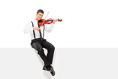 Male violinist playing seated on a blank panel. Isolated on white background Stock Photo