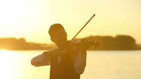 Male violinist playing the violin at the lake at sunset. Violin duet man and woman play violin on nature at the sunset on the lake stock video