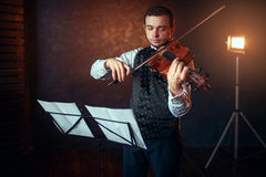 Male violinist with violin against music stand. Portrait of male violinist with violin against music stand. Fiddler man with musical instrument playing in studio Stock Photo