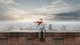 Male violinist. Young man in bow tie playing violin Stock Photo