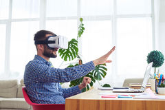 Male in virtual reality glasses orienting in space sitting at ta Royalty Free Stock Images