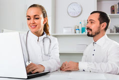Male visitor consulting smiling woman doctor in hospital. Male visitor consulting smiling cheerful women doctor in hospital Stock Photos