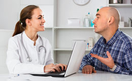 Male visitor consulting smiling woman doctor in hospital Stock Photography